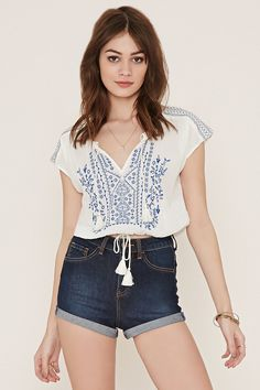 A crinkled woven gauze top with cap sleeves, embroidery on the front and shoulders, a tasseled self-tie neckline, and an elasticized drawstring hem.