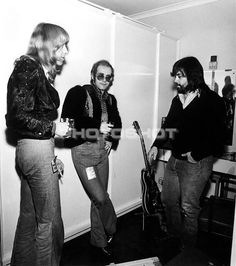 Elton John and guitarist David Johnstone visit Little Feat's Lowell George backstage during the Warner Bros Music Show in the early 1970's.