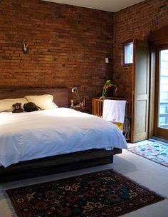 Small windows, hard floors, and brick walls should feel like a basement, but somehow this bedroom just seems warm and inviting.