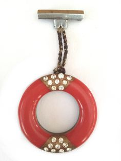 "Art Deco chrome and bakelite dangly brooch with rhinestone decoration. Drop 7.5cm (3""). Hoop diameter 4cm (1 3/4""."