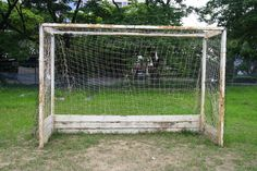 Old soccer goal in field ...  athlete, athletics, ball, big, bleachers, challenge, colour, competition, day, detail, door, empty, european, exercise, fiber, field, football, game, goal, goalline, goalpost, grass, gre, green, ground, hall, horizontal, kick, match, net, nobody, old, olympic, open, outdoor, penalty, play, playground, posts, recreation, score, soccer, sport, stadium, synthetic, team, teamwork, tournament, tree