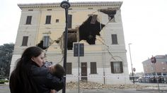 6.0 Earthquake hits Italy: A woman carrying her child stands in front of the damaged town hall building in Sant'Agostino