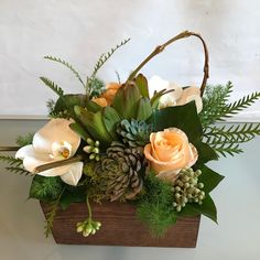 Medium Texture Box with Tiffany roses, succulents, phalaenopsis orchids, berzillia, kalanchoe, leucadendron, grevillia, ming fern, tree ivy, reindeer moss, and fasciated willow in a wooden box.