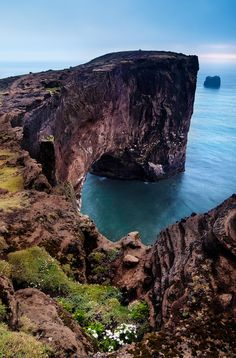 A sea cliff leads off to a point over an archway along de Icelandic coastline near Vic in Iceland