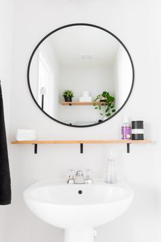 Tiny monochrome powder room with plants, open shelving for storage, a pedestal sink, and a round mirror Tiny Powder Rooms, Modern Powder Rooms, Black Powder Room, Pedestal Sink Bathroom, Modern Pedestal Sink, Pedistal Sink, Concrete Bathroom, Bathroom Vanities, Small Half Baths
