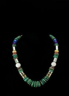 "Tommy Singer Blue Lapis Necklace  Sterling silver and 12K gold filled barrel beads. Genuine Turquoise, Black Onyx, Surgilite, blue Lapis and Coral beads. Necklace is 20"""" and comes with a certificate of authenticity from the Native American artist.   http://www.sterlingjewelrystores.com/product343.html"