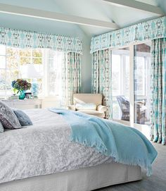 """""""All it needed was paint,"""" Martha says of the home. """"A lot of beach houses are really neutral, but I like when the colors of nature—yellows, greens, blues—explode inside.""""  In this photo: Custom linen drapes frame waterfront views in the master bedroom. The walls are painted Patriotic White by Benjamin Moore. Plus: 19 new ways to decorate your windows »"""