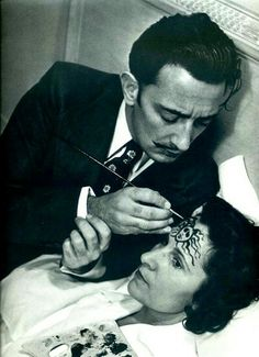 This is Salvador Dali, the renowned artist, painting something on the head of Coco Chanel, renowned fashion designer. She looks like she is in a trance; he looks kind of intense. I don't get it.