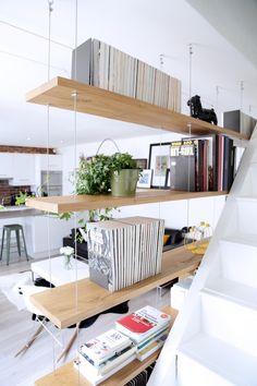 Aménagement d'un appartement - style industriel. Étagères en chêne massif suspendues sur câbles.