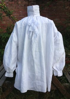Early 19thC linen shirt. The front and back panels are 1 yard square. It is shaped into a shirt by adding triangular inserts to the shoulders and under the arms. The shoulders and armholes are reinforced with double layers of fabric. Sleeves are very wide. Collar stands tall and is fastened with two buttons. Very narrow neck. Fine muslin ruffle to the front. Initials W.F.