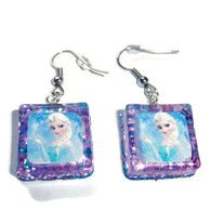 These earrings are made out of resin.The photo embedded in the resin is of Elsa infront of a  blue background. The background of the pendant is blue and purple glitter and is attached to earring hangers. These earrings are inspired by the movie Frozen.  This item would make a perfect gift for a...