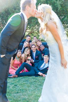Bride & Groom Kissing With Bridal Party Looking On