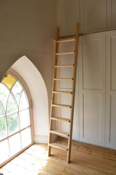 Double decker wardrobe with library ladder for a converted Welsh chapel.