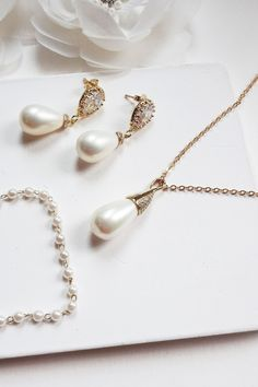Pearl bridal jewelry set made with a gorgeous cream shell pearl teardrop on a gold cubic zircon encrusted bail connected to a lovely chain with pearl earrings and a dainty 3mm pearl bracelet. An extremely elegant design. Very versatile, perfect for a bride, or even as a gift for bridesmaid or mother of the bride. #pearljewelry #weddingjewelry #bridaljewelry