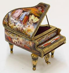 """Miniature Viennese style enamel grand piano music box, executed in the Rococo taste, fashioned as a miniature grand piano housing a music box, the inset panels of courting couples in naturalistic settings, the top opens to reveal painted piano keys and a courting scene, the whole inset within a gilt case with leaf and vine banding, 3.5""""h x 3.5""""w x 5.5""""d"""