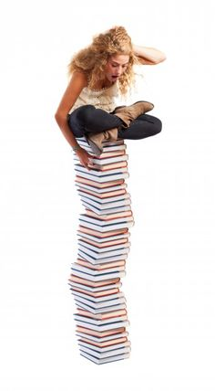 Scared teen sitting on a mountain of books Free Photo
