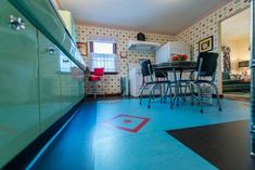 Blue linoleum flooring with insets in this 1940s style kitchen built new