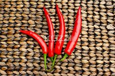 Four Red Chilli Peppers - Four red chilli peppers on a patterned surface