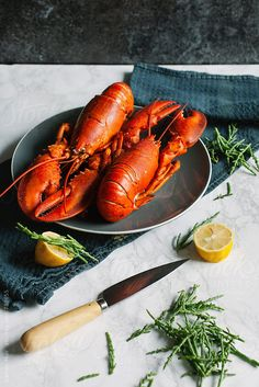 Two cooked lobsters on a plate on a table with samphire and lemon. Live Lobster, Lobster Dinner, How To Cook Lobster, Seafood Pasta, Fish And Seafood, Food Photography Styling, Food Styling, Canadian Lobster, How To Cook Liver