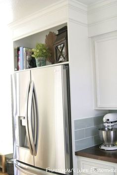 I am LOVING the open space above the fridge We'd need to remove the existing cabinet though.  DIY Refrigerator Enclosure