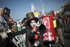 "A demonstrator in a costume depicting a banker and holding a replica of a fire extinguisher for putting out the ""flame"" of an imitation Olympic torch, takes part in a protest against the interim Brazilian president Michel Temer, and the Rio's 2016 Summer Olympics, on the route of the Olympic torch, at the Copacabana beach, in Rio de Janeiro, Brazil, Aug. 5, 2016. (Photo: Leo Correa/AP)"