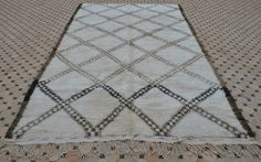11'6 x 6'6  $1765 US Absolutely gorgeous older vintage Beni Ouarain carpet 'old school style'! Densely knotted with a field in ivory and patterned with double lined female lozenges holding intricate smaller patterns and borders in black, charcoal and dark brown. The wool is very soft with that special faint sheen. Medium pile, all wool. In very good condition.