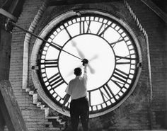 """A workman stops the clock at the Union Depot Railroad Station on the building's final day of operation, Detroit, Michigan. 1971""    (C) Reuther Photo Archive"