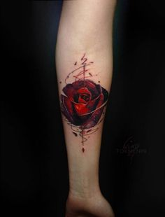 Graphic style red rose tattoo on the inner forearm.