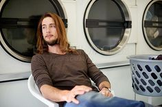 Shot of a young man doing his weekly washing in a laundromat - stock photo #1294983