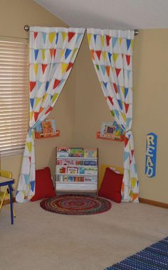 Make a reading corner in kids playroom by just hanging curved shower rod with some shelves, pillows, and a rug.