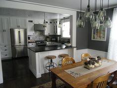 White Kitchen Cabinets, Soapstone Counters, Pottery Barn Paxton Lights, World Market Twist Swivel Stools