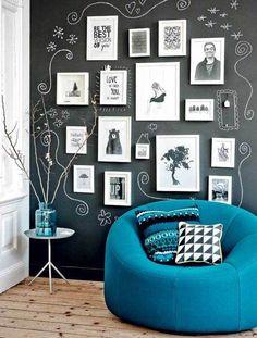 Otra manera de decorar una pared con pizarra es integrarla con la propia decoración. Con esta composición de fotos en blanco y negro y unos toques artísticos a su alrededor queda preciosa.