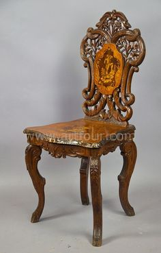 """a carved and inlaid walnut chair with musical work, swiss 1900 a finely carved walnut chair with inlaid seat and back. superb carved edelweiss, gentian and floral ornaments. tilt-seat, inside a musical clock. executed ca. 1900, swiss brienz. height: 37.4"""" (95.0cm), depth: 15.75"""" (40.0cm) price:  EUR 1950.–– (USD 2,260.––)"""