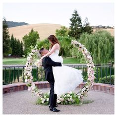 Circle of love round floral arch + lake backdrop.   Outdoor wedding arches