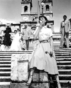 Audrey comiendo helado en la plaza de España. Al fondo, Gregory Peck. Vacaciones en Roma, 1953.