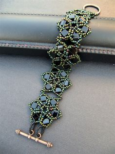 """New Bracelet with Tila Beads - Beading Daily. Materials List: ‐ 8 grams Black Tila Beads ‐ 10 grams green metallic iris seed beads size 11 ‐ 10 grams matte green iris seed beads size 11 ‐ 2 grams opaque black Czech seed beads size 15 ‐ One double‐loop antique copper toggle clasp 1.5"""" in length"""