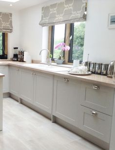 Kitchen window treatment. Modern country style shaker kitchen in Farrow & Ball Cornforth White. From Kitchen & Bedroom Store.