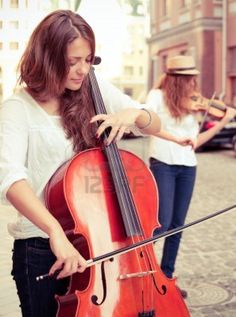 Two women strings duet playing violin and cello on the street of european city. Split toning Stock Photo - 14638549