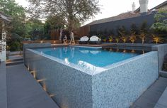 Completed by OFTB Landscape Architecture and Swimming Pool Construction in 2014, this Canterbury project showcases an out of ground swimming pool with featured wet edge and bisazza glass mosaic tile.