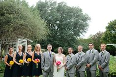The bride and groom pose with their wedding party with navy blue, orange, pink and gray shades for their wedding color palette.
