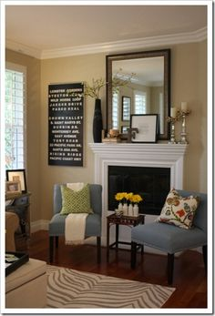 little table between chairs and mantel arrangement
