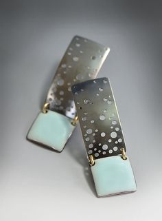 """Pastel Blue Starry Night Enamel Earrings"" Enameled Earrings Created by Reiko Miyagi - Fabricated sterling silver post earrings with a touch of light pastel blue enamel. Gold-filled jump rings give a contrasting accent. Hand drilled holes let the background light pass through reminiscent of a starry sky. The sterling silver has a dark oxidized finish. Due to the hand drilling no two star patterns are alike making each pair unique. $86.00"