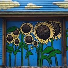 Sunflower painting on garage door. Look at the clouds on the roof! So cute!