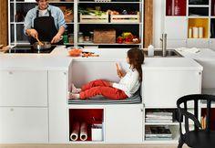 Ein Vater, der in einer METOD Küche an einer Kücheninsel kocht. Seine Tochter sitzt daneben auf einer Bank aus TUTEMO Regalen in Weiß/Rot, die in die Kücheninsel integriert ist.