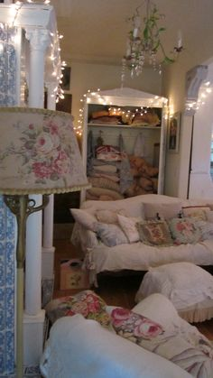 Extra pillows and old feather paisley and rose eiderdowns--oh, and also love those fairy lights!