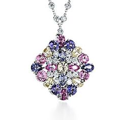 """A delightful mosaic of pink, purple and yellow sapphires hangs from a diamond chain or can be worn as a brooch. Pendant with round and pear-shaped fancy sapphires and round brilliant diamonds in platinum."""