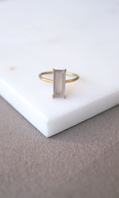 Delicate and simple gemstone ring with a baguette cut gray chalcedony. The modern ring is made out of sterling silver and with 14k gold plating.