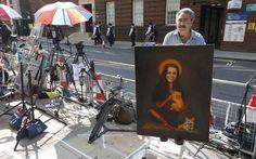 18/7 - O artista Kaya Mar posa com um quadro feito para a espera do bebê real em frente ao hospital St. Mary's. Suzanne Plunkett/Reuters
