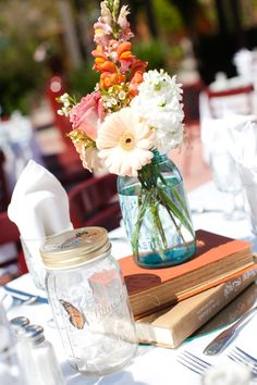 Wedding Reception centerpiece: hardback books in wedding colors with a BALL blue mason jar on top filled with peach, white, and terracotta colored flowers. A faux butterfly in a jar (electronic that moves when the table is bumped or the jar is tapped).