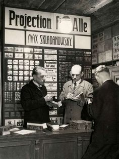 Max Składanowski (left) behind the counter in his shop, where he sells stereo slides c1890s-1900s